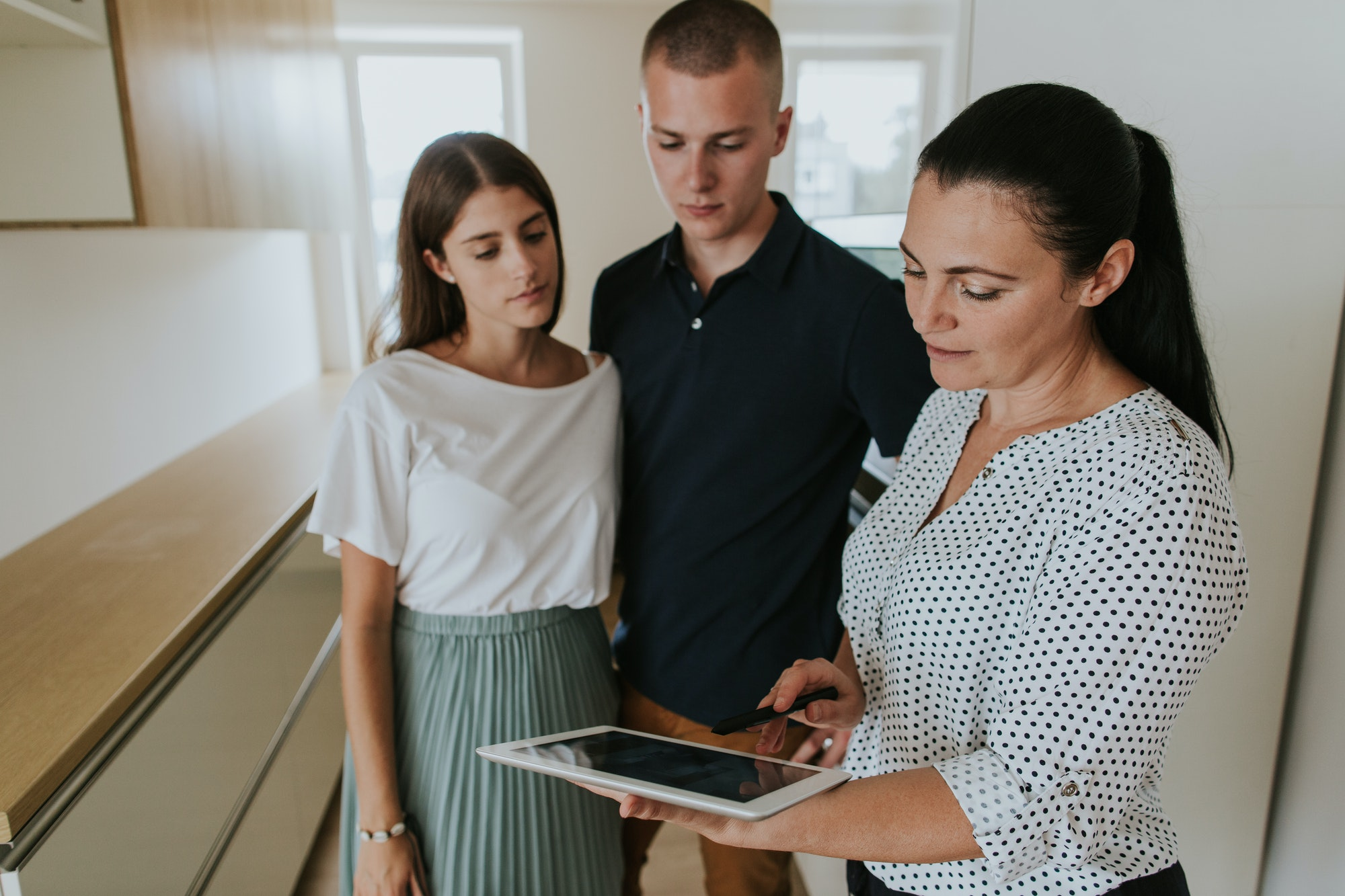 Estate agent using digital tablet showing young couple new house.